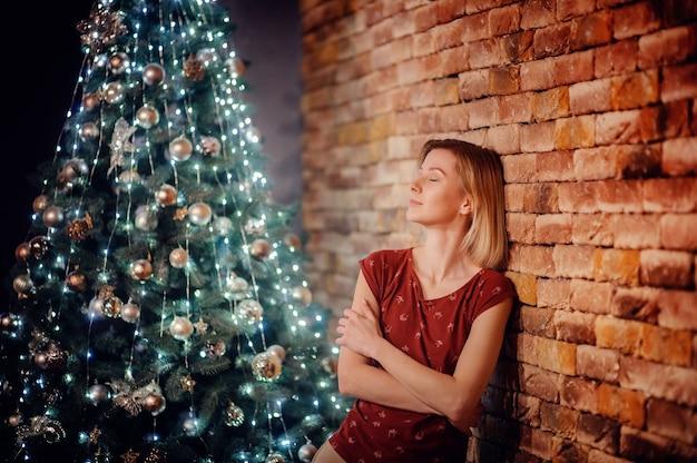 Portret van blond haar jong meisje met glimlach in rode t-shirt leunde op bruine bakstenen muur voor grote hoge verlichte kerstboom vol lichten van garland. nieuwjaar thuis concept