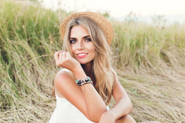 Portret van blond meisje met lang haar poseren voor de camera op de achtergrond van een veld. ze houdt gras vast en kijkt naar de camera.