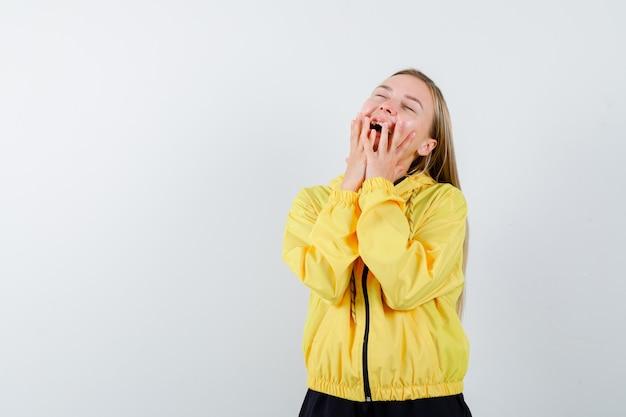 Portret van blonde dame die handen op wangen in trainingspak houdt en zalig vooraanzicht kijkt