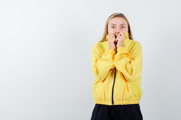 Portret van blonde dame die kraag op haar gezicht in trainingspak trekt en bang vooraanzicht kijkt