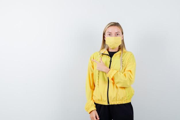 Portret van blonde dame die naar links wijst in trainingspak, masker en bang vooraanzicht kijkt
