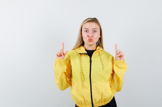 Portret van blonde dame die omhoog wijst, lippen pruilend in trainingspak en op zoek schattig vooraanzicht