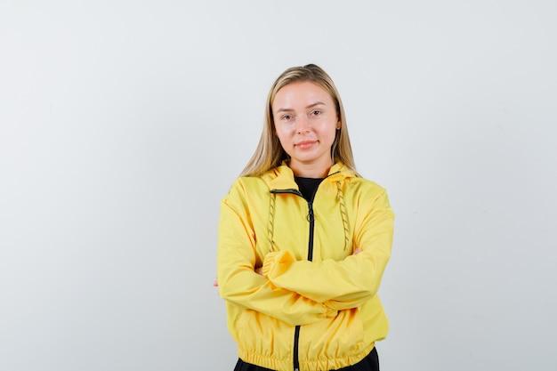 Portret van blonde dame met armen gevouwen in trainingspak en op zoek naar zelfverzekerd vooraanzicht