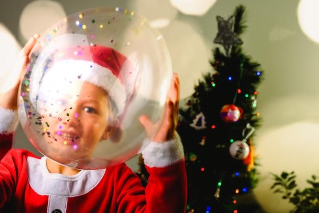 Portret van blonde en knappe 5-jarige jongen als santa claus op de voorgrond