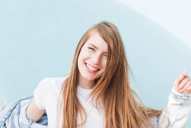 Portret van blonde haren vrouw die lacht op blauwe achtergrond