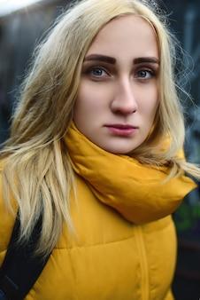 Portret van blonde hipster tiener meisje selfie maken close-up, ze draagt gele jas en rugzak