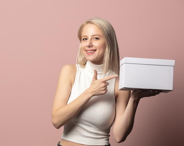 Portret van blonde in bovenkant met witte giftdoos op roze