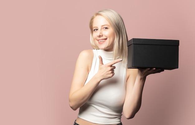 Portret van blonde in bovenkant met zwarte giftdoos op roze
