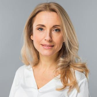 Portret van blonde jonge vrouw die camera tegen grijze achtergrond bekijkt