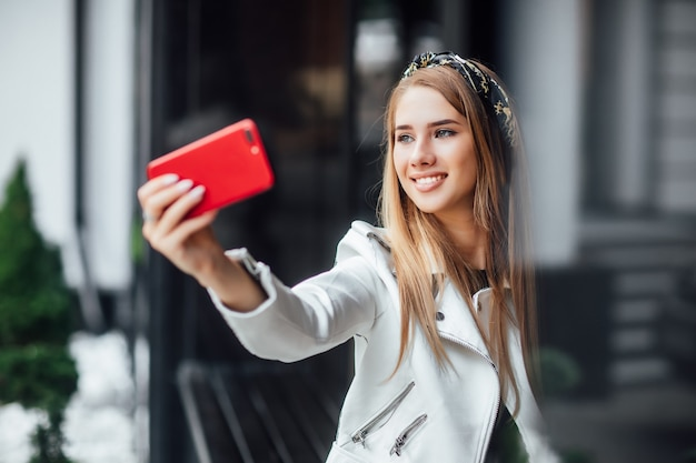 Portret van blonde jonge vrouw maakt een selfie door rode telefoon in de straat.