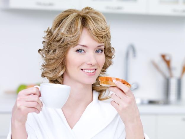 Portret van blonde jonge vrouw met gelukkige glimlach die een ontbijt in de keuken hebben