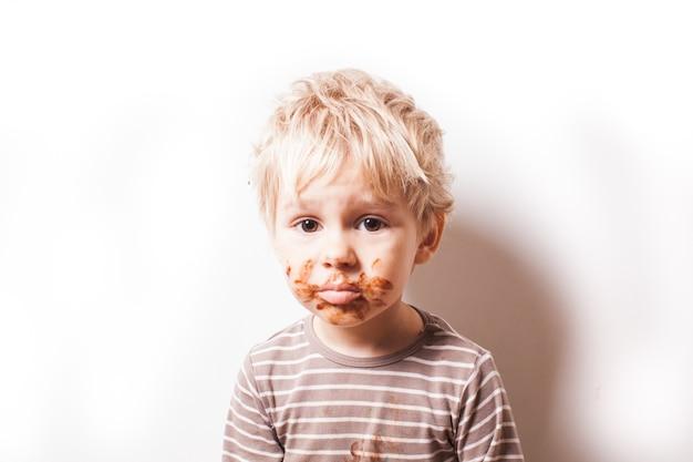 Portret van blonde jongen met chocolade op zijn gezicht geïsoleerd op wit