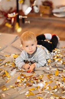 Portret van blonde jongetje in grijze trui en zwarte spijkerbroek liggend op bed onder confetti en voorzijde te kijken