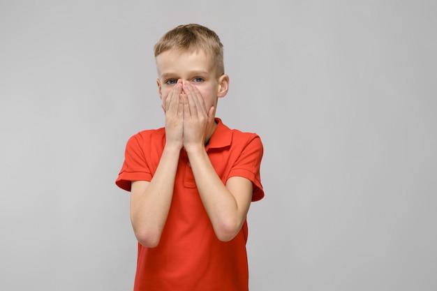 Portret van blonde kaukasische droevige kleine jongen in oranje t-shirt die zijn mond sluiten met handen op grijze achtergrond