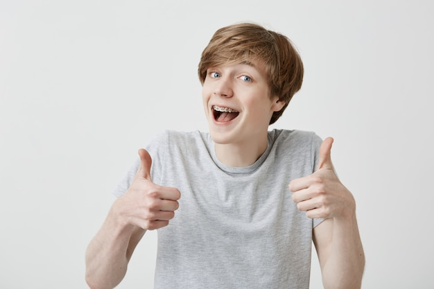 Portret van blonde mannelijke student of klant met brede glimlach, kijken naar de camera met gelukkige uitdrukking, thumbs-up met beide handen tonen, het bereiken van studiedoelen. lichaamstaal