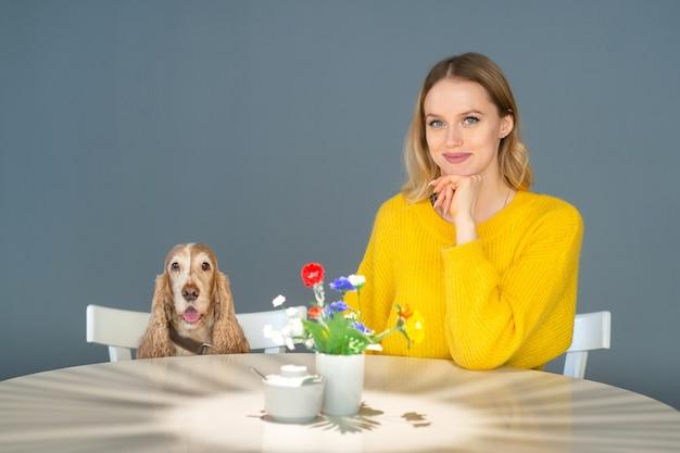 Portret van blonde meisje zitten aan de tafel met haar vriendelijke cocker spaniel puppy en op zoek