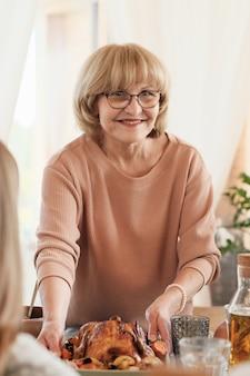 Portret van blonde rijpe vrouw in bril geserveerd schotel met kalkoen op tafel voor thanksgiving day