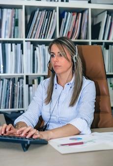 Portret van blonde secretaresse met hoofdtelefoon die met computer in bureau werkt