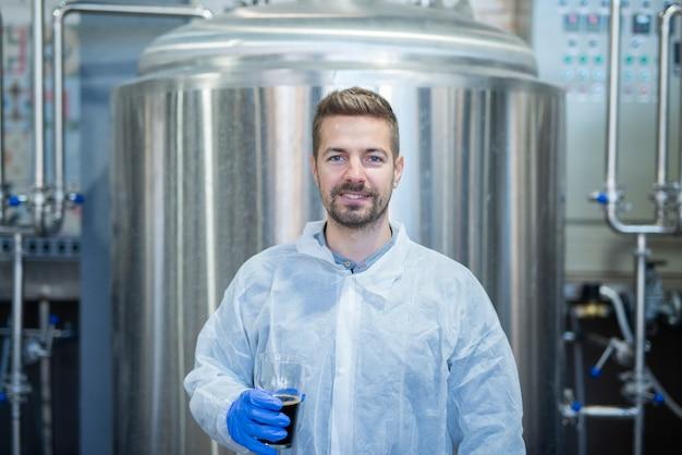 Portret van blonde technoloog die glas drankproduct houdt bij de productielijn van het fabrieksbier