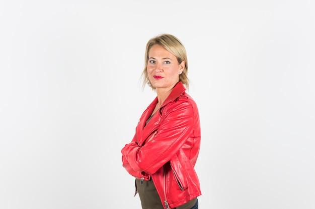 Portret van blonde volwassen vrouw in rood lederen jas met gekruiste armen staande tegen een witte achtergrond