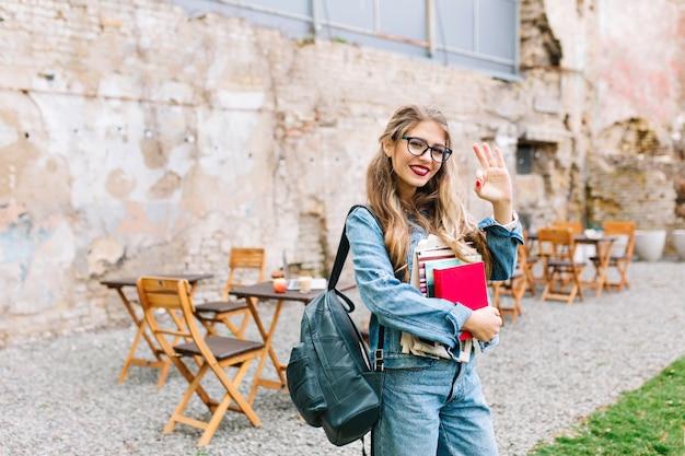 Portret van blonde vrij vrouwelijke student die boeken met openluchtkoffie op de achtergrond draagt. mooi blondemeisje in glazen die ok handteken tonen en nota's houden.