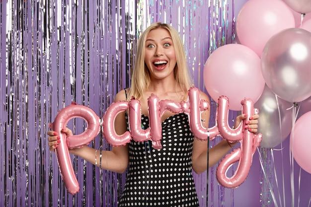 Portret van blonde vrolijke vrouw in polka dot jurk, houdt ballonnen betekenis partij, maakt foto met decoraties, lacht van goede emoties, speciale gelegenheid viert met familieleden. vrijgezellenfeest