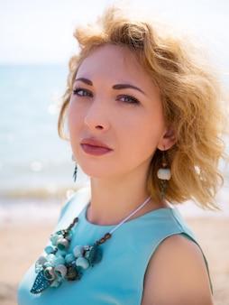 Portret van blonde vrouw die blauwe kleding draagt