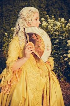 Portret van blonde vrouw gekleed in historische barokke kleding met ouderwets kapsel, buitenshuis. luxe middeleeuwse jurk