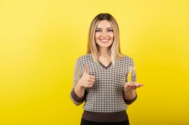Portret van blonde vrouw met glas water duimen opgevend.