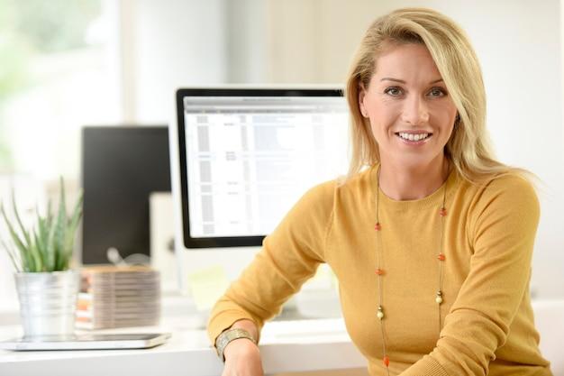 Portret van blonde vrouw op middelbare leeftijd in bureau
