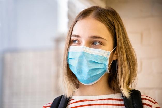 Portret van blonde vrouwelijke student in de buurt van raam in wegwerp blauw masker. op de universiteit tijdens coronavirus covid lockdown. studente met beschermend medisch masker.