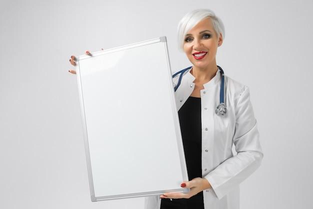 Portret van blondevrouw in artsenkostuum met een magnetisch raad in haar die handen op achtergrond wordt geïsoleerd
