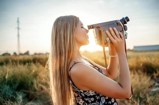 Portret van blondevrouw in bloemendrukkleding met uitstekende videocamera op druivengebied tijdens zonsondergang