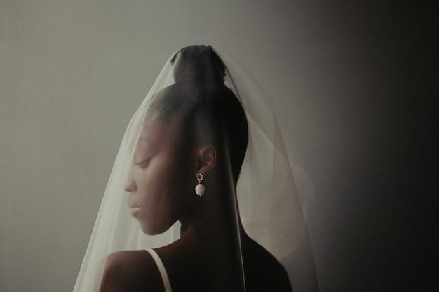 Portret van blozende bruid in trouwjurk en sluier