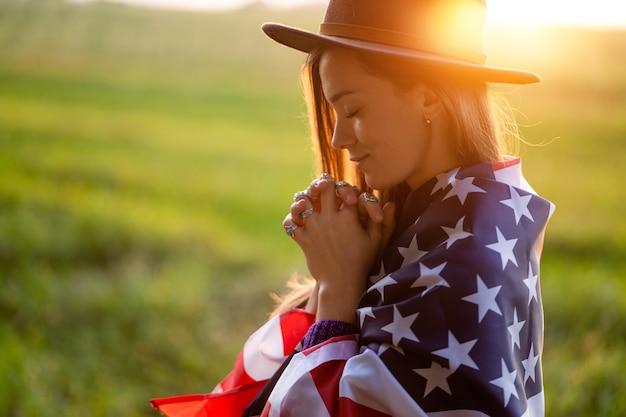 Portret van boho chique vrouw in hoed met amerikaanse vlag die zilveren ringen met turkooise steen dragen bij zonsondergang. sieraden indie meisje met hippie stijl en boho mode. reis naar amerika