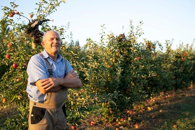 Portret van boomgaard landarbeider met armen gekruist trots staande door appelbomen.
