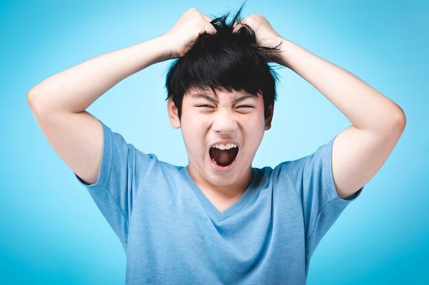 Portret van boos aziatisch jong geitje op blauw.