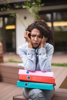 Portret van boos dame zittend op een bankje met kleurrijke mappen en helaas