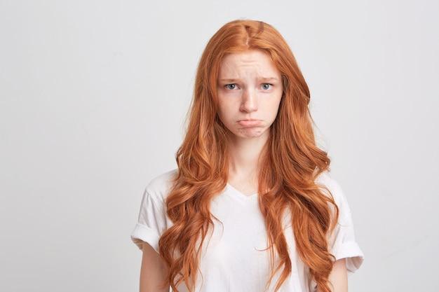 Portret van boos depressieve jonge vrouw met rood golvend lang haar en sproeten draagt t-shirt voelt zich bezorgd en ongelukkig geïsoleerd over witte muur