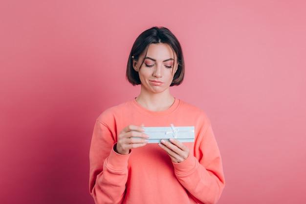 Portret van boos gefrustreerd meisje openen geschenkdoos geïsoleerd op roze achtergrond