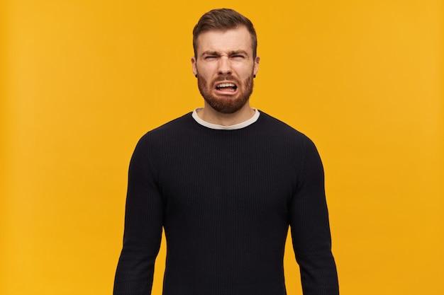 Portret van boos, huilend mannetje met donkerbruin haar en varkenshaar. heeft piercing. het dragen van een zwarte trui. emotie concept. geïsoleerd over gele muur