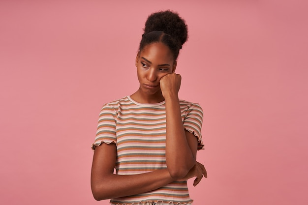 Portret van boos jong bruinharig krullend wijfje met haar wang op opgeheven hand leunend terwijl zij droevig opzij kijkt, geïsoleerd over roze muur