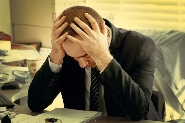 Portret van boos kantoormedewerker, manager man zit achter de monitor van de computer.