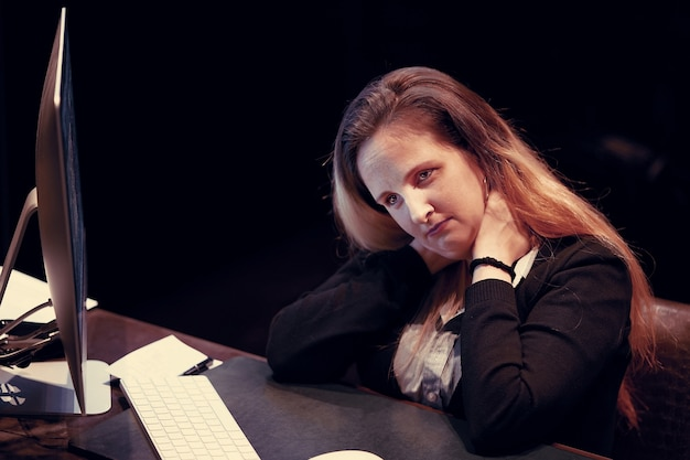 Portret van boos kantoormedewerker, manager vrouw zit achter de monitor van de computer.