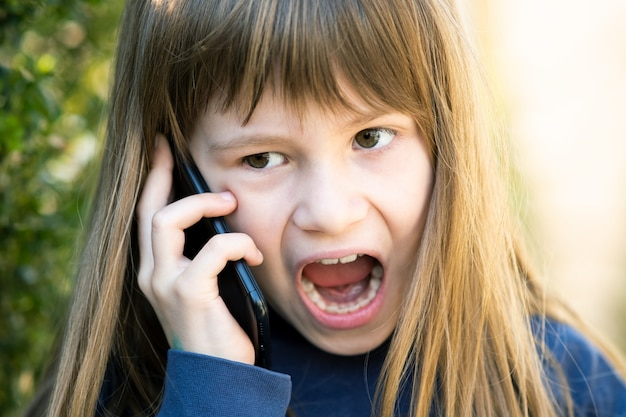 Portret van boos kindmeisje met lang haar dat op celtelefoon spreekt. kleine vrouwelijke jongen met discussie over smartphone. kinderen communicatieconcept.