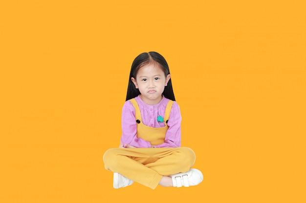 Portret van boos klein aziatisch kindmeisje in roze