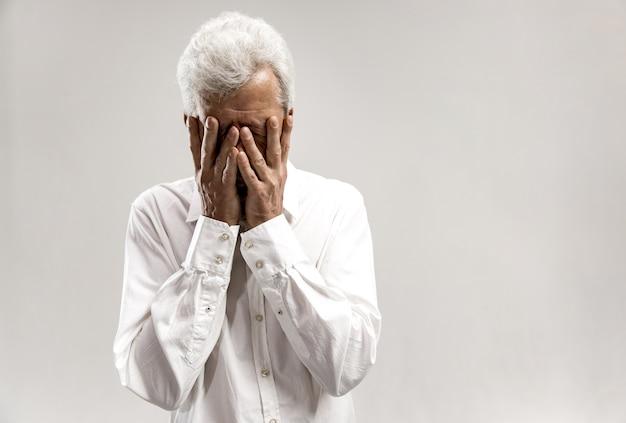 Portret van boos oude man die gezicht bedekt tijdens het huilen. geïsoleerd op grijze muur