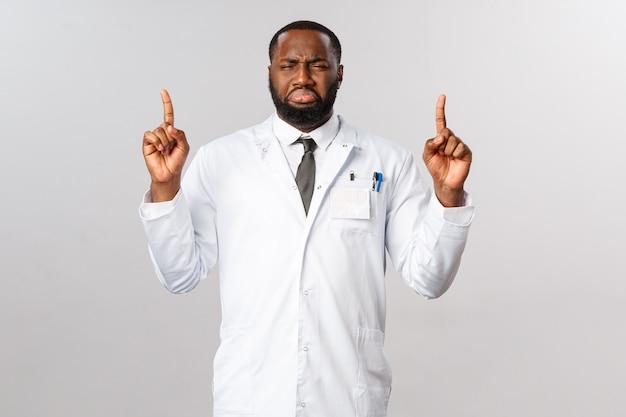 Portret van boos, sombere afro-amerikaanse verpleger of arts wijzende vingers en klagen over overbelasting, geladen schema in het ziekenhuis, moe werken tijdens covid19 pandemie, corona-uitbraak