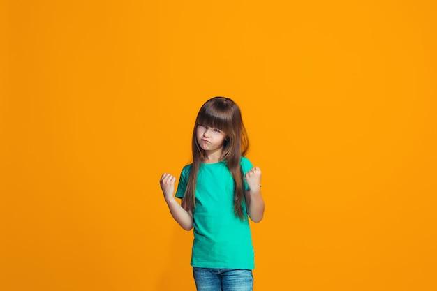 Portret van boos tienermeisje op een oranje studioachtergrond