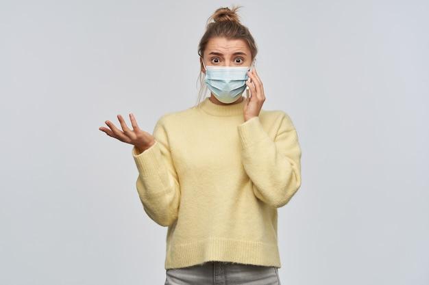 Portret van boos, verontwaardigd meisje met blond haar verzameld in een broodje. gele trui en beschermend gezichtsmasker dragen. praten aan de telefoon. kijkend naar de camera, geïsoleerd over witte muur